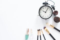 Female cosmetics and accessories with alarm clock on white background with copy space Royalty Free Stock Photos