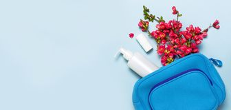 Female cosmetics bag, cosmetic products, white cosmetic containers, pink flowers on pastel blue background top view flat lay copy stock photos