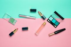 Female cosmetics for make-up layout on a pastel background. Cosmetic shadows, make-up brush, eyeshadow lipstick, perfume bottle. Flat lay, top view. Copy space stock photography