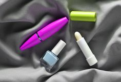 Female cosmetics: mascara for eyes, nail polish, hygienic lipstick on a gray silk fabric, top view. Female cosmetics: mascara for eyes, nail polish, hygienic stock photography