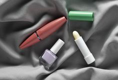 Female cosmetics: mascara for eyes, nail polish, hygienic lipstick on a gray silk fabric, top view. Female cosmetics: mascara for eyes, nail polish, hygienic stock images