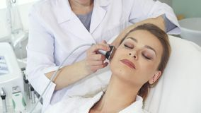 Cosmetologist makes facial massage with special equipment stock photography