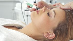 Cosmetologist using ultrasonic scrubber on client`s face stock video