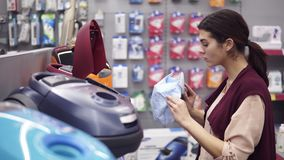 Female costumer choosing vacuum cleaner in appliance store. Coming up to a showcase row taking a dustbag out of vacuum. Cleaner and examining it carefuly stock footage