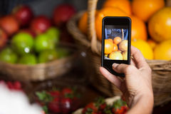 Female costumer taking picture of oranges on mobile phone in organic section. Of supermarket stock images