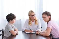 Female counselor holding hand of upset teenage girl. Sitting near brother on therapy session royalty free stock photos