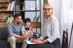 Female counselor writing in clipboard and looking at camera while father and son sitting on therapy. Session stock photo