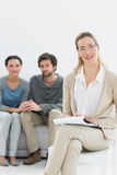 Female counselor with young couple in background. In her office royalty free stock photo