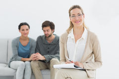 Female counselor with young couple in background. In her office stock photo
