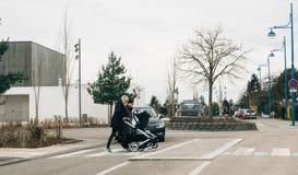 Female couple crossing street pushing stroller. STRASBOURG, FRANCE - APR 2, 2018: Volkswagen black car lets female couple crossing street pushing stroller Royalty Free Stock Photos
