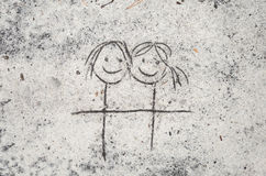 Female couple drawing on sand background. Closeup to female couple drawing on sand background Stock Photos