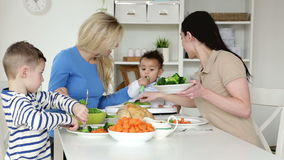 Female couple having dinner with their children stock footage
