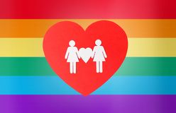Female couple pictogram on red heart over rainbow. Gay pride, homosexual, valentines day and lgbt concept - female couple white paper pictogram on red heart over stock photography