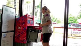 Female courier collecting letters from mailbox stock footage
