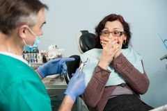 Female covering her mouth with both hands at the dentist appointment in the dental clinic Royalty Free Stock Photo