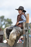 Female cowboy wearing chaps in Ecuador. May 27, 2017 Sangolqui, Ecuador: young female cowboy wearing chaps sitting on wooden fence during a rural rodeo stock photo