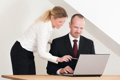 Female coworker helping male colleague. Nice office setting with wooden table and two coworkers. Female helping male colleauge with the grey laptop Royalty Free Stock Photography