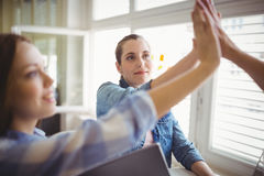 Female coworkers giving high-five in creative office Royalty Free Stock Images