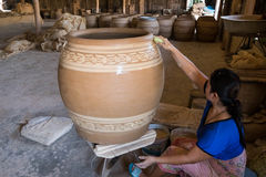 Female craftperson uses wet sponge to dub the pattern on big clay pot. Stock Images