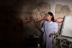 Female crazy scientist holding large iron sickle in dungeon Royalty Free Stock Photos