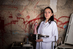 Female crazy scientist holding a severed hand and eyeball in a b. Ox in front of a blood splattered wall, Halloween concept Stock Photos
