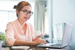 Female creative designer holding a cup of coffee. Young Asian Female creative designer wear glasses holding a cup of coffee with laptop computer at her royalty free stock image