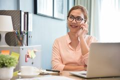 Female creative designer talking on cell phone at her workplace. stock photography