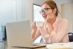 Female creative designer thinking. Young Asian Female creative designer thinking and working with laptop computer and holding a cup of coffee at her workplace royalty free stock image