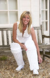 Female cricketer putting on pads. Woman putting on her cricket pads outside the pavilion stock photo