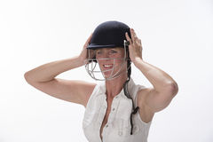 Female cricketer putting on safety helmet Stock Photos