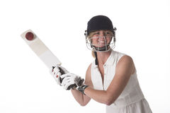 Female cricketer in safety helmet hitting a ball. Smiling woman wearing a safety helmet hitting cricket ball with a bat stock photography