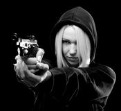 Female criminal with hood on head shooting with gun Royalty Free Stock Photo