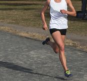 Female Cross Country runner racing on a gravel path. A high school female cross country runner runner racing on a gravel path wearing a white top and black pants Stock Photos