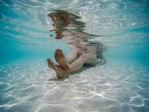 Underwater picture of a young woman lying down on the beach shore. Clear blue water stock images