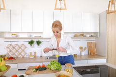 Female culinary blogger holds phone in hands and composes compos Royalty Free Stock Photos