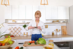 Female culinary blogger holds phone in hands and composes compos Royalty Free Stock Images