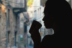 Female with cup of tea opposite a narrow streets of the old town of Verona. Italy stock photos