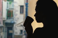 Female with cup of tea opposite a narrow streets of the old town of Verona. Italy stock photography