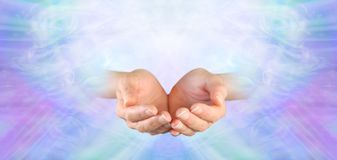 Healing offered with Unconditional Love. Female cupped hands on a subtle pink purple blue green flowing energy background Royalty Free Stock Photography