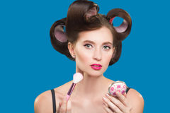 Female in curlers applying rouge. makeup brush. Royalty Free Stock Image
