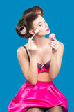 Female in curlers applying rouge. makeup brush. Stock Photography