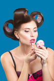 Female in curlers applying rouge. makeup brush. Stock Images