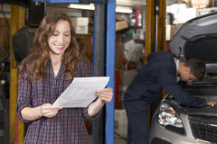 Female Customer In Auto Repair Shop Satisfied With Bill For Car. Customer In Auto Repair Shop Satisfied With Bill For Car Repair Stock Image