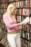 Female customer in bookshop. Reading a book Stock Photography