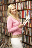 Female customer in bookshop. Smiling at camera Stock Images