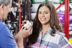 Female Customer Buying Guinea Pig From Salesman. Portrait of happy female customer buying guinea pig from salesman in pet store Royalty Free Stock Photography