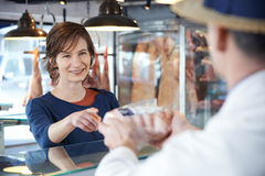 Female Customer Buying Meat In Butchers Shop. Female Customer Buys Meat In Butchers Shop Royalty Free Stock Photo