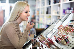 Female customer buying red lipstick in makeup section Royalty Free Stock Image