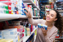 Female customer buying toothpaste. Positive female buying toothpaste for sensitive teeth in store Stock Image