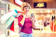 Female customer with cellular phone and shopping bags in the mall stock photography